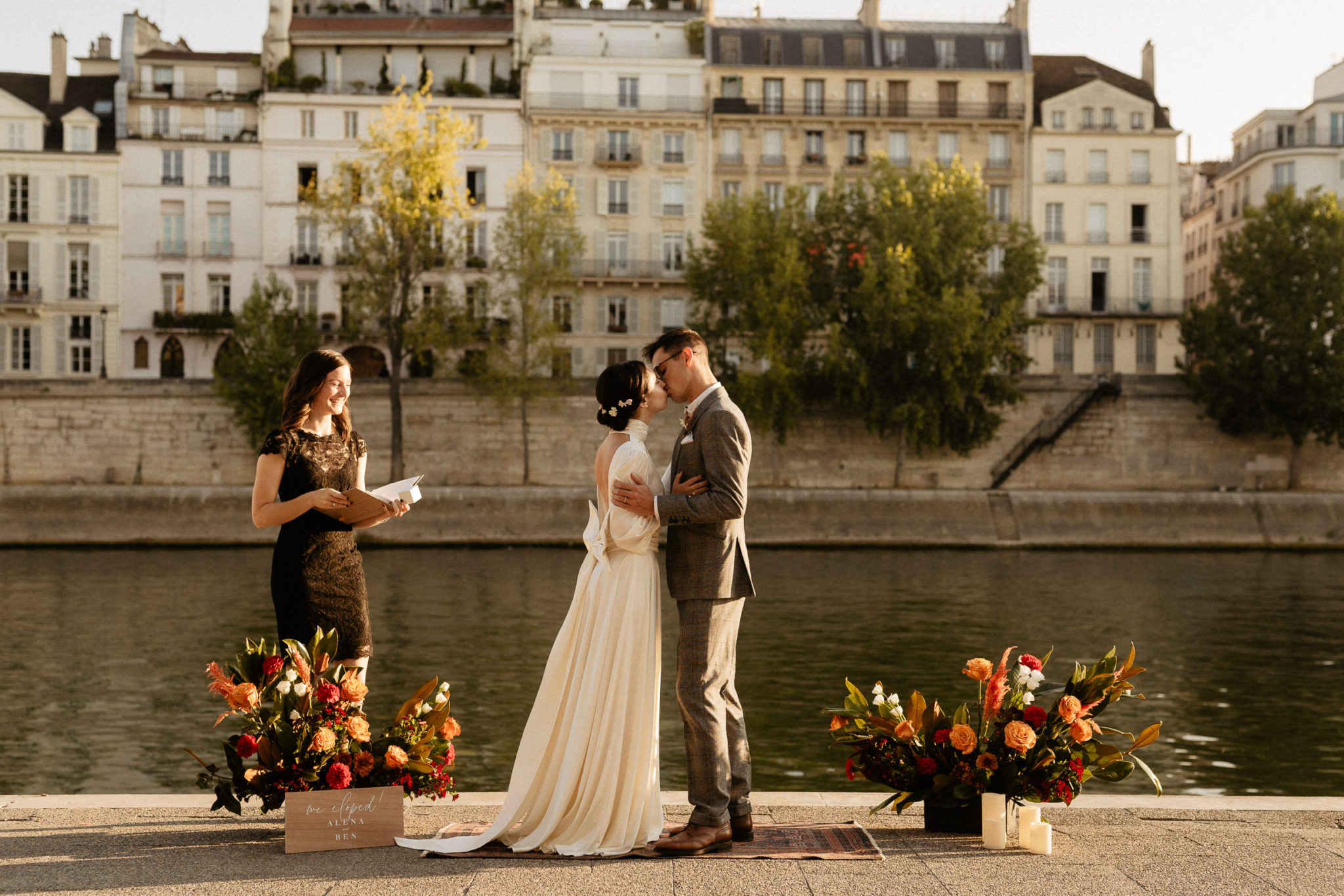 Elopement by the seine with couple kissing & flowers and officiant